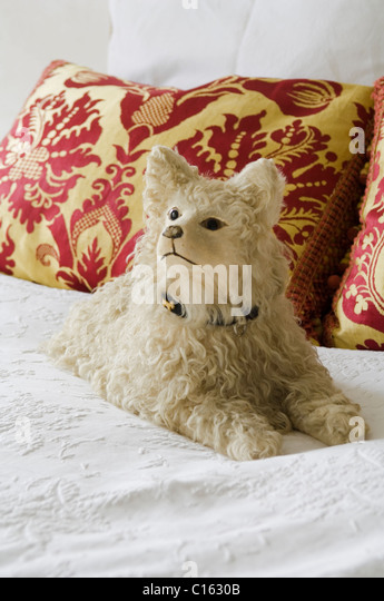 Cuddly dog toy on white bedding with baroque patterned cushions - Stock-Bilder