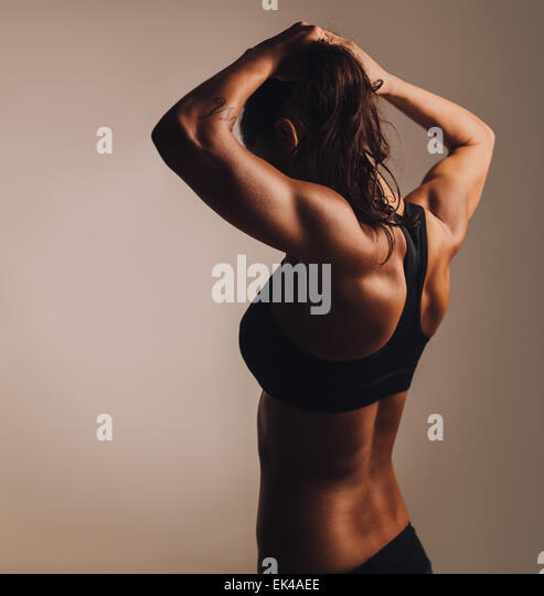 Rear view of young woman bodybuilder showing muscular body. Fitness female showing muscular back. - Stock Image