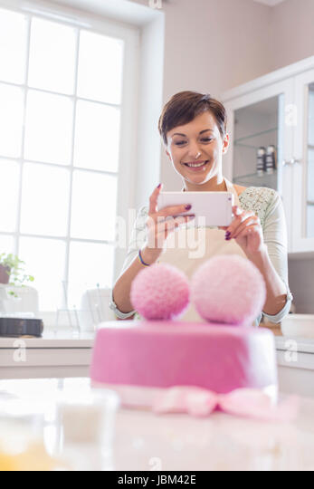 Female caterer with camera phone photographing pink wedding cake in kitchen - Stock-Bilder