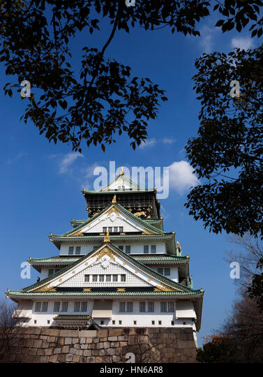 OSAKA, JAPAN - March 14 : The main tower of Osaka Castle framed by trees in the castle grounds in Osaka, Japan on - Stock Image