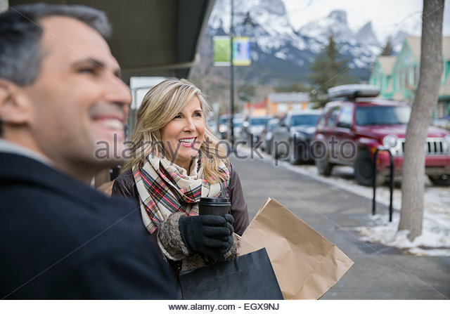 Couple with shopping bags and coffee on sidewalk - Stock Image