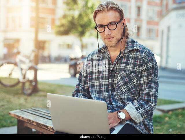 Entrepreneur with laptop sitting outside working. City lifestyle - Stock Image