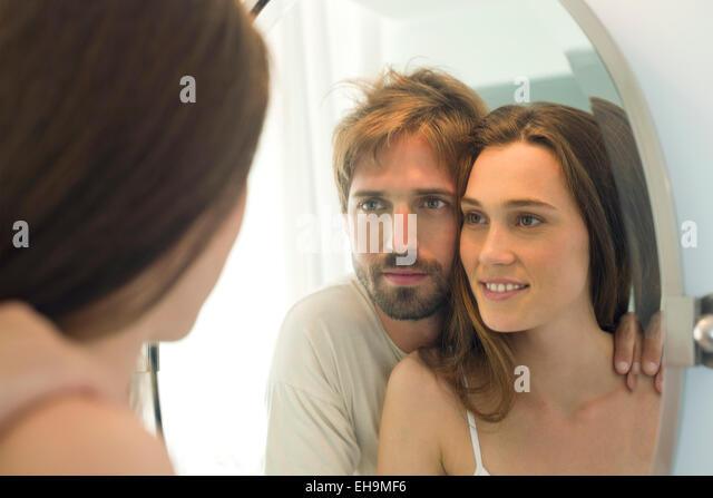 Couple looking in bathroom mirror together - Stock-Bilder