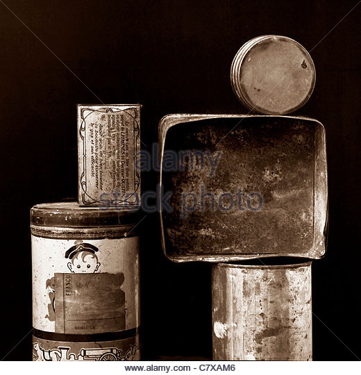 Old tin cans and boxes stacked on top of each other - Stock Image