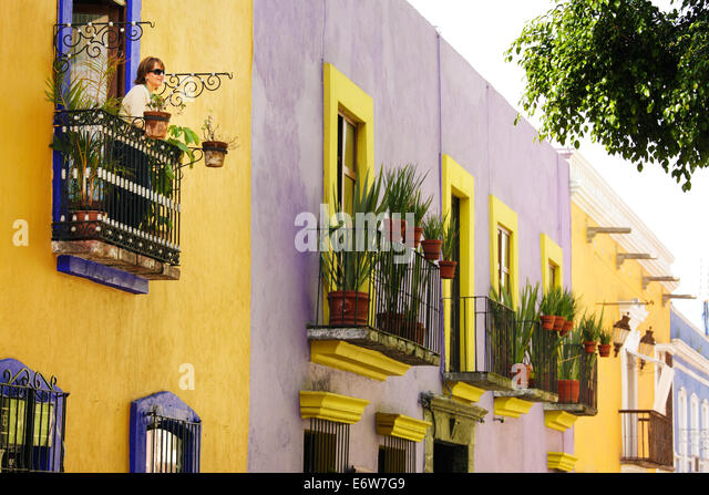 A tourist looks out at Callejon de los Sapos, a colorful street in Puebla, Mexico. - Stock Image