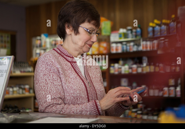 Owner of health foods store using smartphone - Stock Image