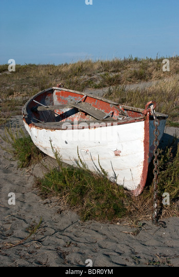 abandoned old double ended rusting row boat beached on a grassy dune in Fort Worden State Park near Port Townsend - Stock Image