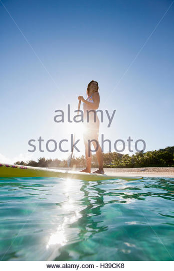 Young Woman Standing On Paddleboard In Water - Stock Image