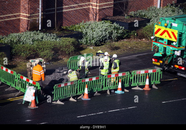 Workman digging up the road - Stock Image