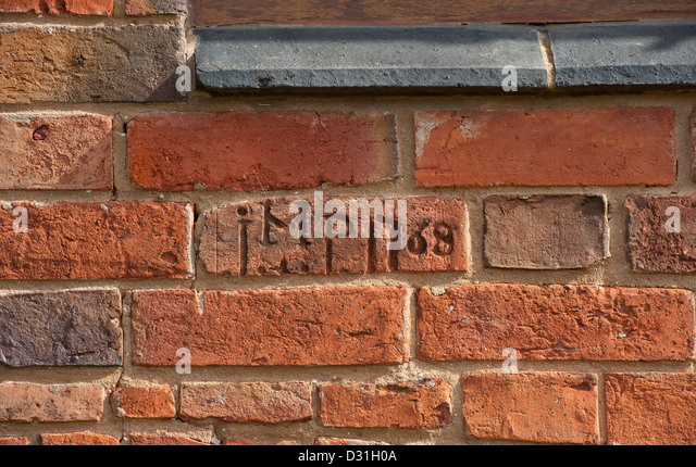 Initials and date etched into brickwork on a newly renovated barn in rural England. - Stock Image