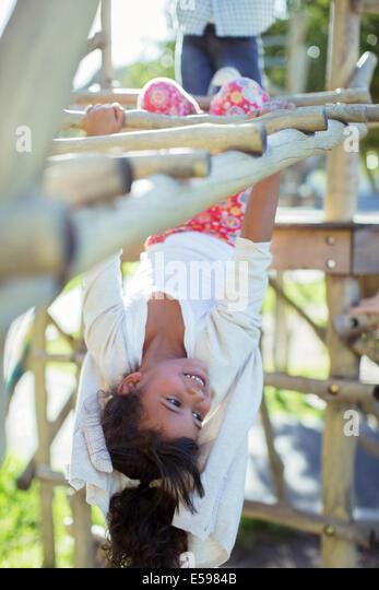 Girl climbing on monkey bars on playground - Stock Image