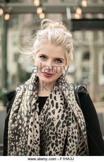 Portrait of beautiful young woman wearing leopard print scarf - Stock Image