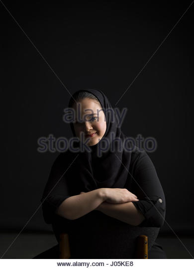Portrait smiling Middle Eastern woman against black background - Stock Image