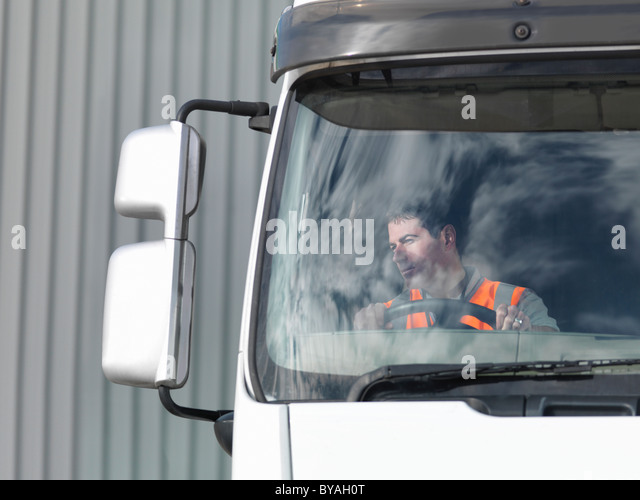 Driver looking in truck mirror - Stock Image