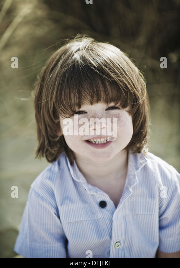 Young boy with brown hair and freckles wearing blue shirt England - Stock Image