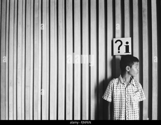 Front View Of Boy Standing Against Wall - Stock Image