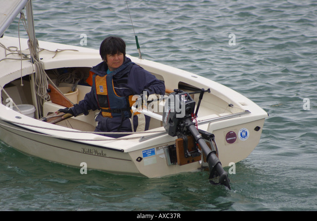 white rowing boat outboard motor raised sailor river rother rye east sussex england - Stock Image