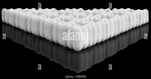 Multiple white pills on black with reflection - Stock Image