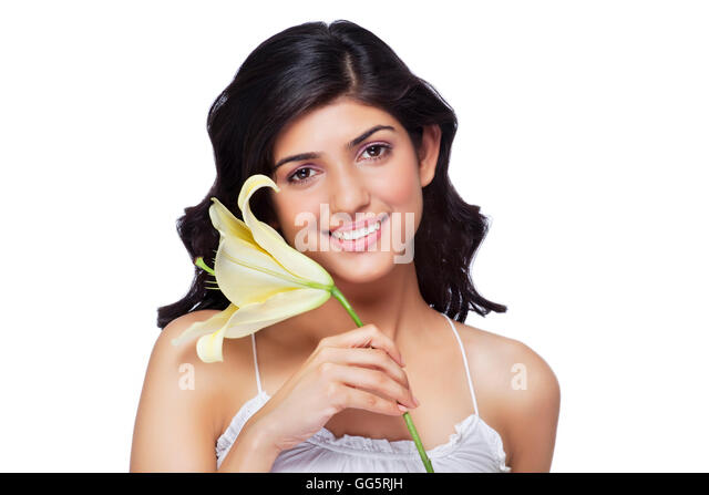 Portrait of young female with flower against white background - Stock-Bilder