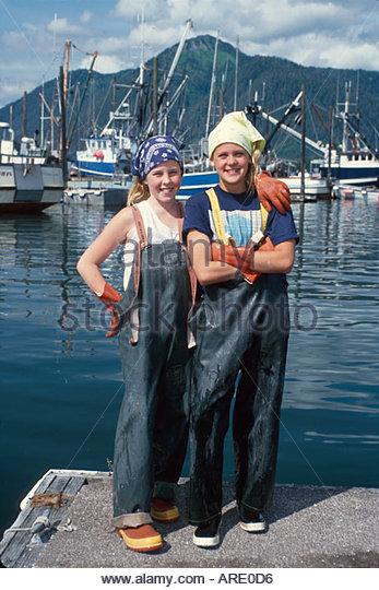 Alaska Petersburg Norwegian descendents fishing village girls slickers clean commercial fishing boats - Stock Image