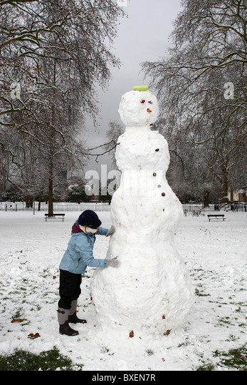 A woman is making a snowman after heavy snowfall in Kennigton Park, London, UK on December 18th, 2010. - Stock Image