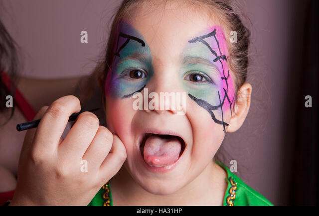 Little girl with tongue out while she is made up by make-up artist - Stock Image
