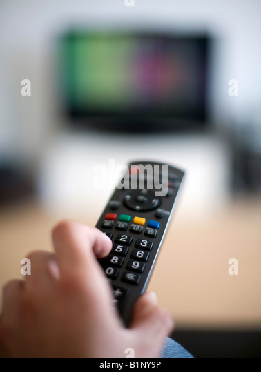 A hand held Remote Control being used on a television - Stock Image