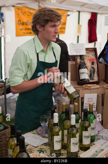 England, Shropshire, Ludlow.  A young man at the Ludlow Food Festival selling wine from the Frome Valley Vineyard. - Stock Image
