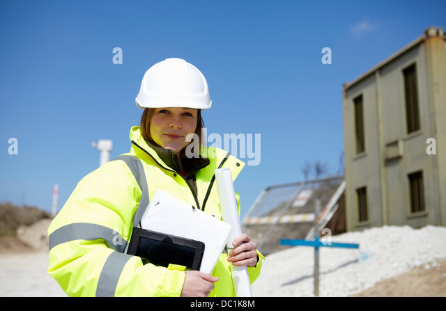 Portrait of female with blueprint and digital tablet on construction site - Stock-Bilder