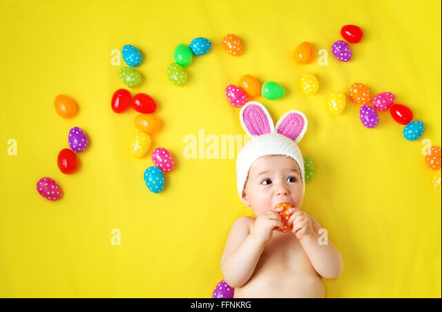 Baby boy in bunny hat lying on yellow blanket with easter eggs - Stock Image