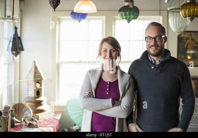 Two people standing in a store full of antique objects a couple running a business - Stock Image
