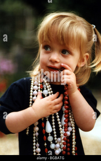 Photograph of young girl dressed up beads jewellery nervous kids - Stock-Bilder