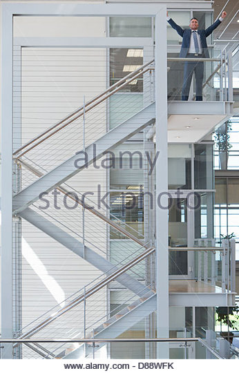 Exuberant businessman at top of stairs in office - Stock Image