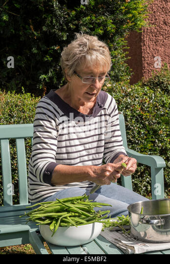 Older woman with rheumatoid arthritis in garden UK slicing home-grown green/runner beans ready for freezing for - Stock Image