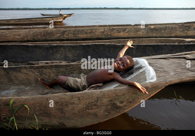 A boy relaxes in a dugout canoe on the Congo River, Yangambi, Democratic Republic of Congo, Africa - Stock-Bilder