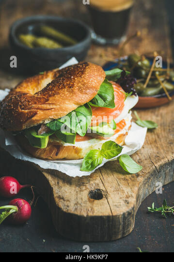 Breakfast with bagel with salmon, avocado, cream-cheese, basil and espresso coffee, rustic wooden board background, - Stock Image