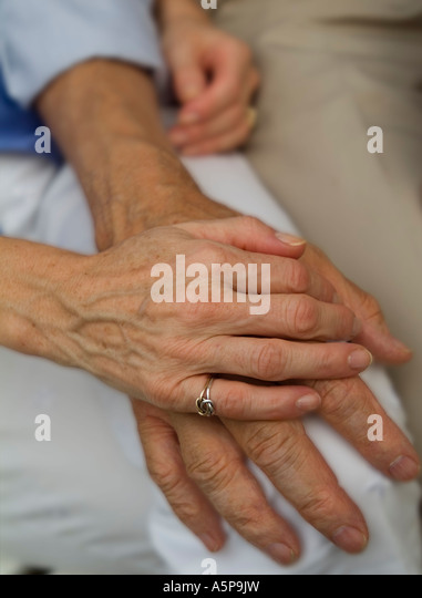 Caring couple holding hands. - Stock Image