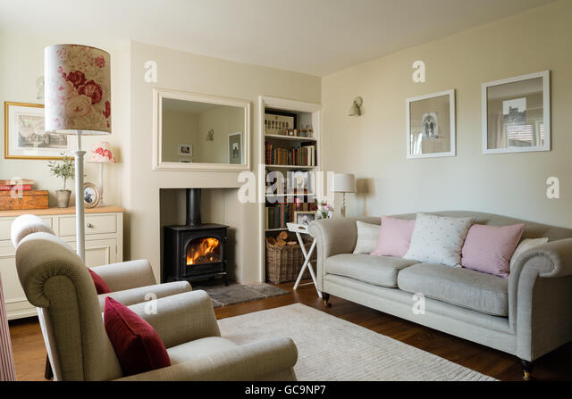 Cosy cottage sitting room with wood burning stove and linen upholstered sofa - Stock Image