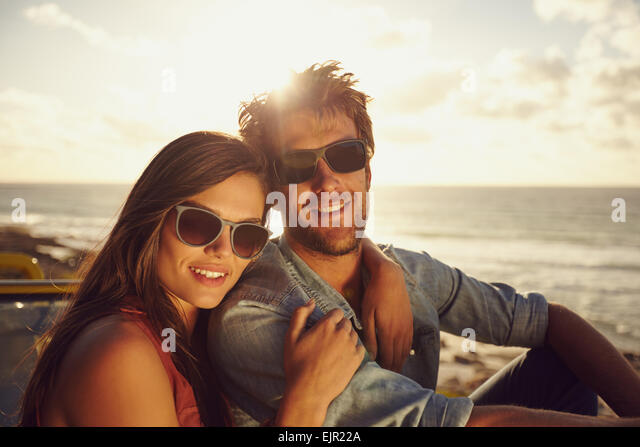 Portrait of beautiful young couple wearing sunglasses looking at camera while on a road trip. Young man and woman. - Stock Image