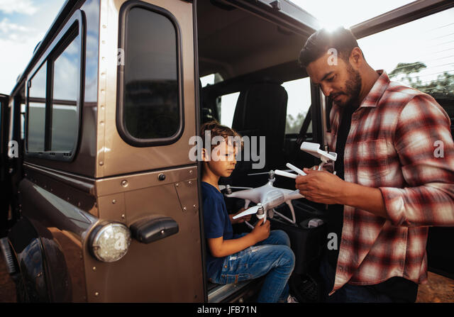 Shot of father and son at the back of their car setting up a drone to fly. Young man and son assembling a drone - Stock Image