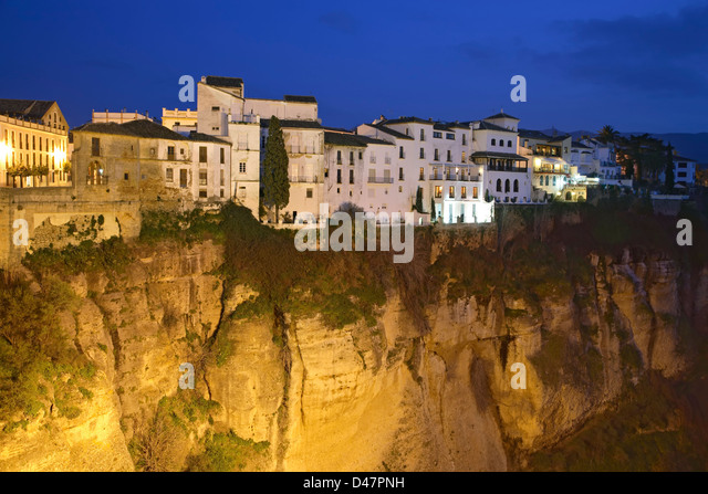 Houses atop cliff at twilight, Ronda, Spain - Stock Image