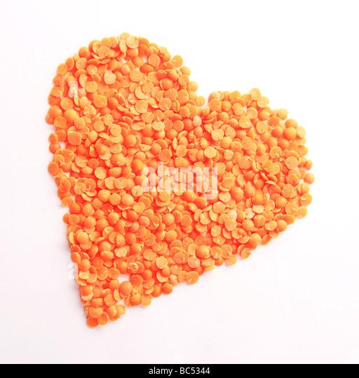 Orange Split Lentils in Heart Shape - Stock Image