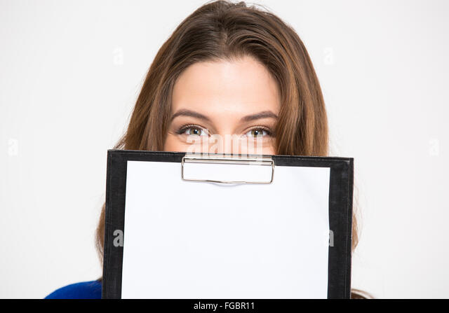 Closeup of cute lovely young woman hiding behind blank clipboard over white background - Stock Image