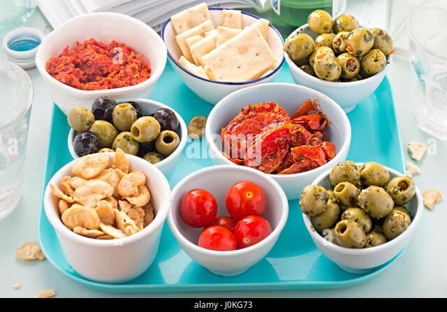 Spanish tapas on blue tray - red pesto, olives, cherry tomatoes, red pesto, crackers - Stock Image