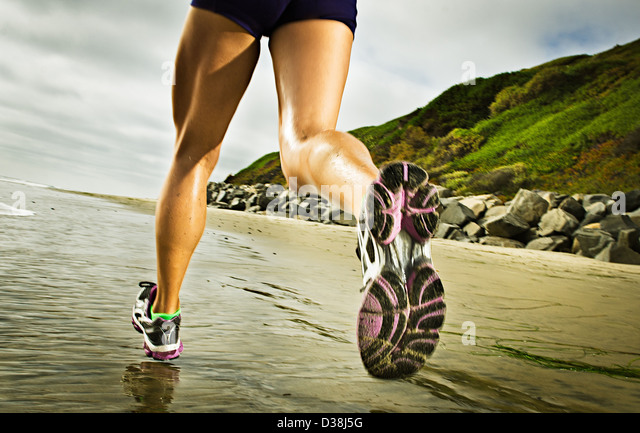 Close up of woman running on beach - Stock Image