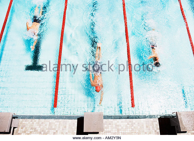 Three swimmers coming to ledge of pool - Stock Image