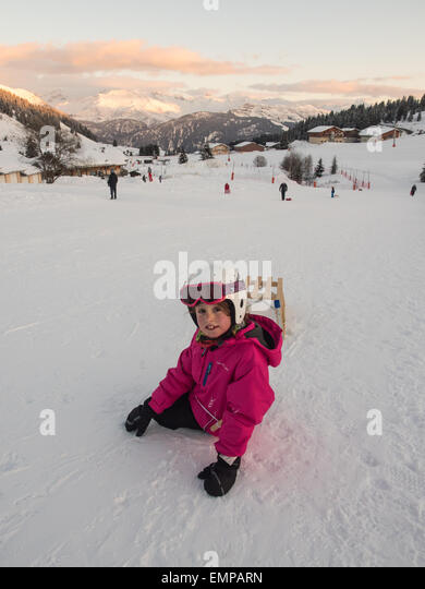 small smiling girl in ski clothes and helmet playing on the piste with a sledge under evening light with mountain - Stock Image