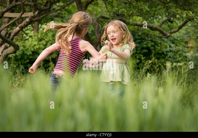 Girls running together in tall grass - Stock Image
