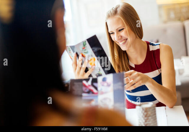 Two beautiful women looking at menu in restaurant and smiling - Stock Image