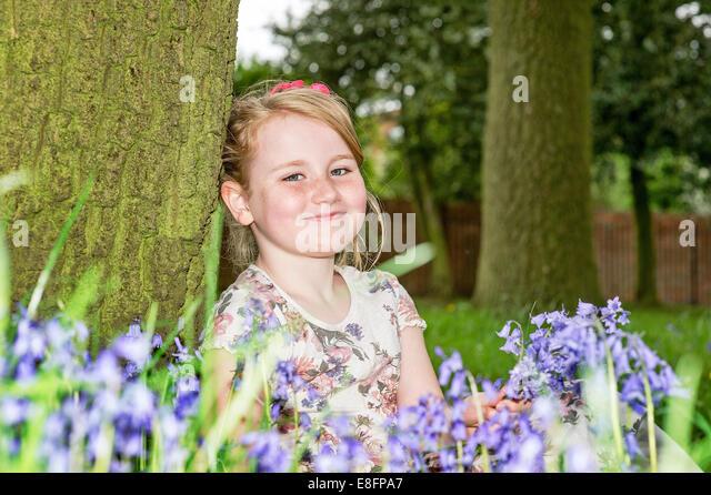United Kingdom, UK, West Midlands, Warwickshire, Rugby, Portrait of girl (8-9) smiling among flowers - Stock Image